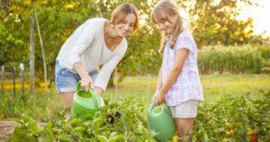 Meisje in een gastgezin geeft mee de planten van de moestuin water - fille arrose les plantes chez sa famille d'acceuil