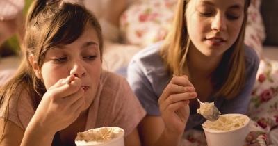 Meisjes op uitwisseling eten een ijsje op bed - filles pendant un échange mangent une glace